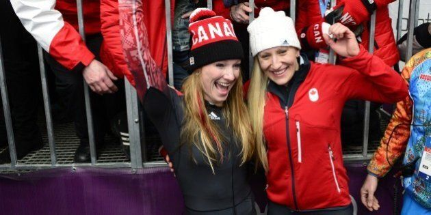 Gold Medallist, Canada-1 two-woman bobsleigh pilot Kaillie Humphries (R bottom) and brakewoman Heather Moyse celebrate with family and friends after the Women's Bobsleigh Heat 4 and final run at the Sliding Center Sanki during the Sochi Winter Olympics on February 19, 2014.        (Photo credit should read JOHN MACDOUGALL/AFP/Getty Images)