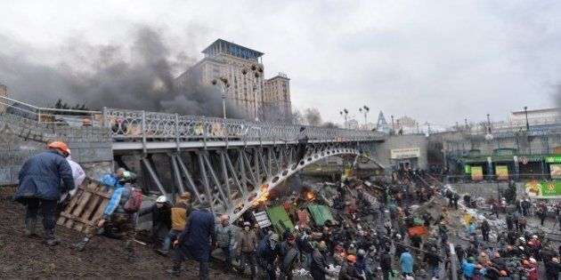 Anti-government protesters reinforce a barricade during clashes with the police in the center of Kiev...