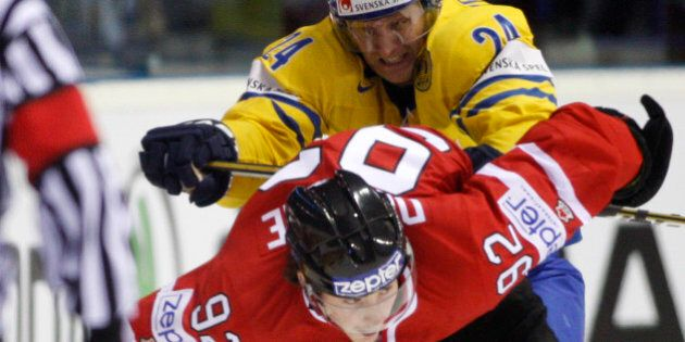 Sweden's Staffan Kronwall, back, fights for a puck with Matt Duchene, front, from Canada during their...