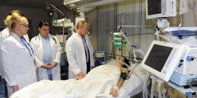 President Vladimir Putin (2nd R) visits Russian freestyle skier Maria Komissarova in a hospital in Sochi on February 15, 2014. 23-year-old Maria Komissarova sustained a broken back in a fall while training on the ski-cross course during the Sochi 2014 Winter Olympic Games . AFP PHOTO/ RIA-NOVOSTI/ POOL/ MIKHAIL KLIMENTYEV (Photo credit should read MIKHAIL KLIMENTYEV/AFP/Getty Images)