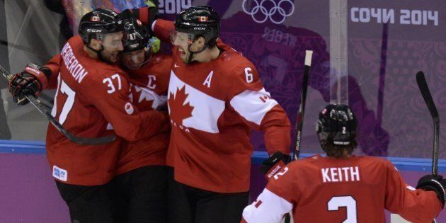 Canada's Sidney Crosby (2L) celebrates with teammates after scoring during the Men's ice hockey final Sweden vs Canada at the Bolshoy Ice Dome during the Sochi Winter Olympics on February 23, 2014.  AFP PHOTO / ALEXANDER NEMENOV        (Photo credit should read ALEXANDER NEMENOV/AFP/Getty Images)