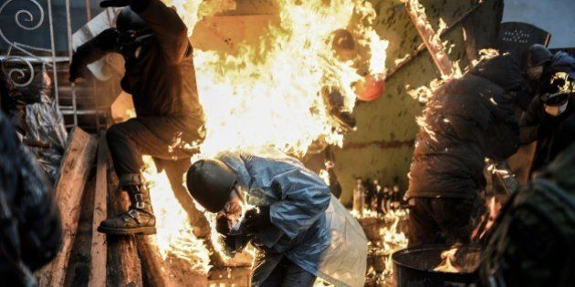 Protesters burn as they stand behind burning barricades during clashes with police on February 20, 2014...