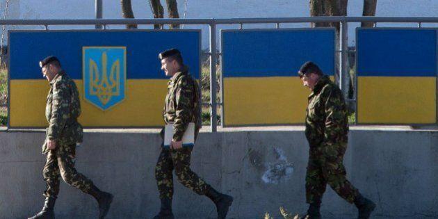 Russian officers walk past the Ukrainian marine battalion headquarters in the Crimean city of Feodosia...