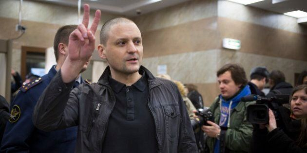 Russian opposition activist Sergei Udaltsov shows victory sign as he greets journalists in a court room...