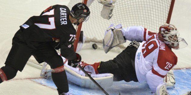 Canada's Jeff Carter scores past Austria's goalkeeper Bernhard Starkbaum during the Men's Ice Hockey...