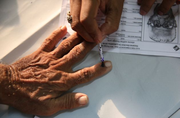 An elderly Indian citizen gets ink mark on his finger prior to voting at a polling center during the...