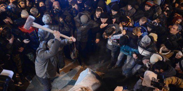 KIEV, UKRAINE - DECEMBER 8: An Ukrainian protester smashes Vladimir Lenin statue with sledgehammer as...