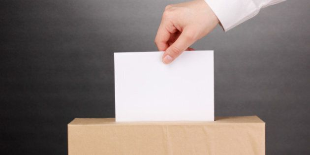 hand with voting ballot and box