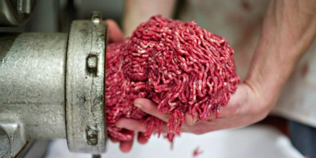 Butcher Justin Taylor collects ground beef as it exits the grinder at the Wyanet Locker in Wyanet, Illinois,...