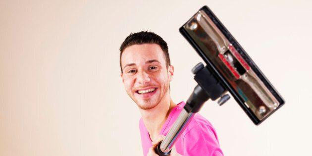 Happy young man with vacuum