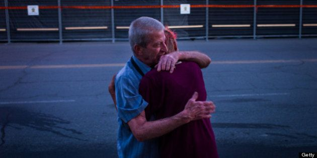 LAC-MEGANTIC, CANADA - JULY 14: Marcel Larrivee (L) comforts Patricia Landry after the pair first witnessed...