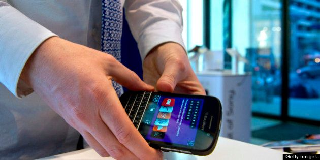 Geoffrey Newsome, sales consultant, prepares to install a BlackBerry Q10 for display at a Bell Canada retail location in Toronto, Canada, on Tuesday, April 30, 2013. BlackBerry, the Canadian smartphone maker, climbed to its highest level in more than a month after Chief Executive Officer Thorsten Heins said he sees sales of its new Q10 device to be in the 'tens of millions.' Photographer: Galit Rodan/Bloomberg via Getty Images
