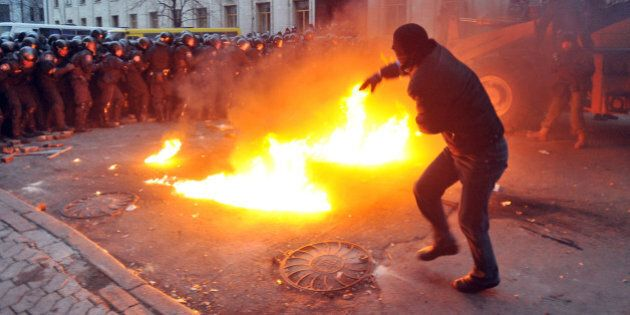 A protester throws stones towards riot police during the storming of the Viktor Yanukovych Presidential...