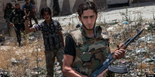 Syrian rebel fighters belonging to the 'Martyrs of Maaret al-Numan' battalion leave their position after...