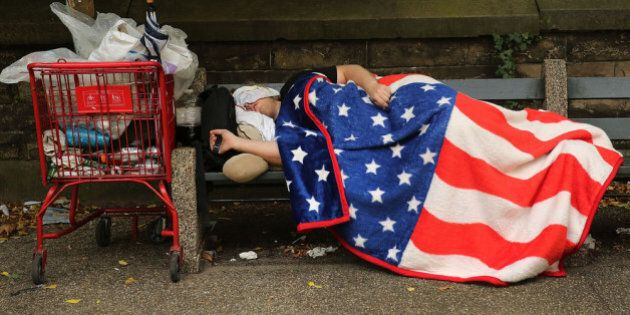 NEW YORK, NY - SEPTEMBER 10: A homeless man sleeps under an American Flag blanket on a park bench on...
