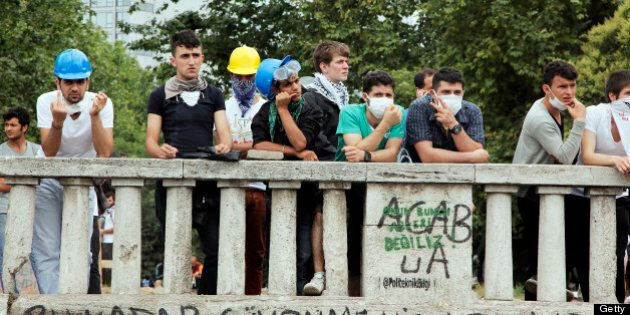 Demonstrators wait at the entrance of the Taksim Gezi park on June 12, 2013 after a night of running...
