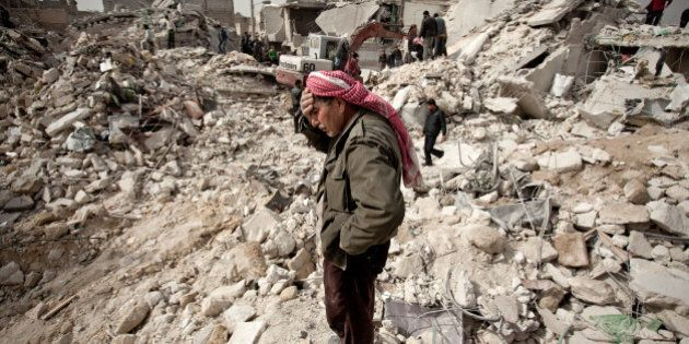 A Syrian man reacts while standing on the rubble of his house while others look for survivors and bodies...