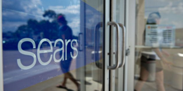 A shopper exits a Sears store in Peoria, Illinois, U.S., on Friday, Aug. 16, 2013. Sears Holdings Corp....
