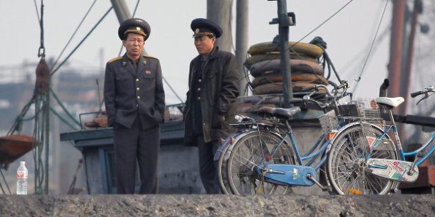 North Korean officials wait by the docks along the bank of the Yalu River in the North Korean town of...