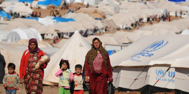 Syrian internally displaced people walk in the Atme camp, along the Turkish border in the northwestern...