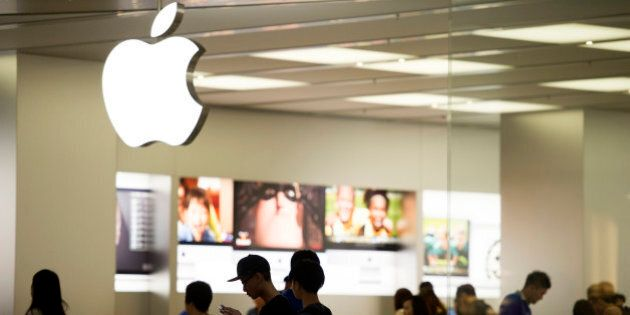 A man looks at his Apple Inc. iPhone in front the company's store in Hong Kong, China, on Tuesday, July...