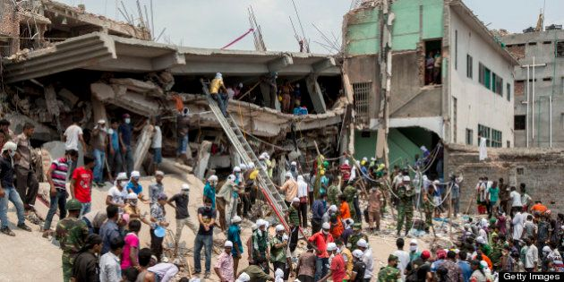 Rescue workers and volunteers search by hand for victims amongst the debris of the collapsed Rana Plaza...