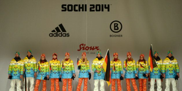 Models and German athletes hold the German flag as they present the official German olympic team's outfit for the next Olympic wintergames in Sotchi, during a fashion show at the Duesseldorf fair ground, western Germany, on October 1, 2013. AFP PHOTO / PATRIK STOLLARZ        (Photo credit should read PATRIK STOLLARZ/AFP/Getty Images)