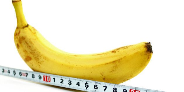 Large banana and measuring tape on a white