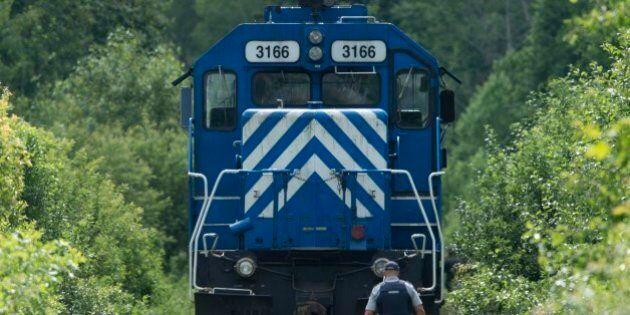 LAC-MEGANTIC QC - JULY 9:An RCMP officer secures a grouping of locomotives that were involved in the...