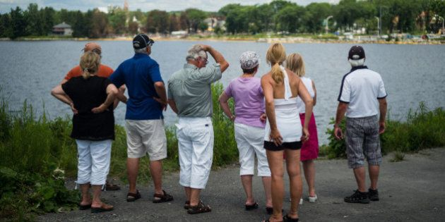 LAC-MEGANTIC, CANADA - JULY 14: People look out toward the 'red zone' crash site, on July 14, 2013 in...