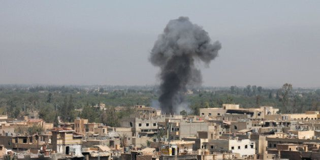 TOPSHOTS - Smoke rises from buildings in Syria's eastern town of Deir Ezzor on August 13, 2013 following...