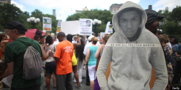 NEW YORK, NY - JULY 14: People gather at a rally honoring Trayvon Martin with his photo standing (R)...