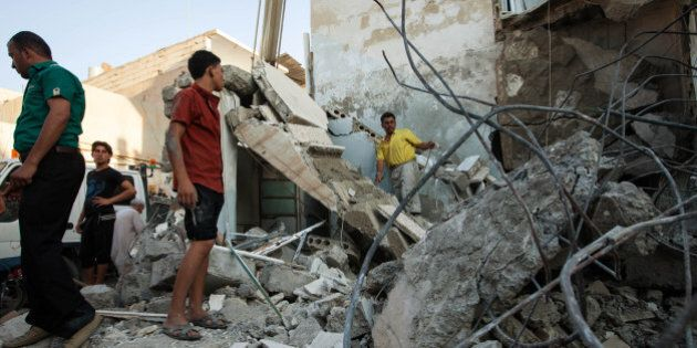 Syrians inspect debris after a bomb hit a building during clashes between rebel fighters and Syrian government...