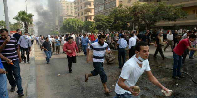 Egyptian Muslim Brotherhood supporters run from police in a street leading to Rabaa al-Adawiya protest...