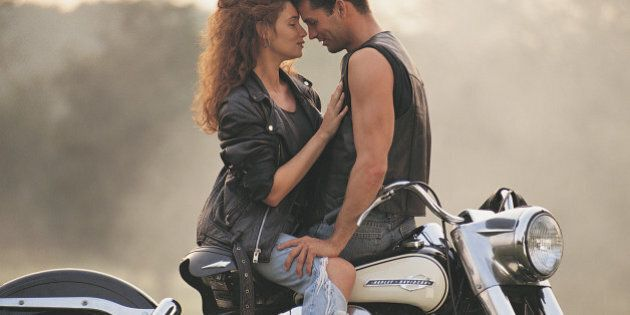 Passionate couple posing on motorcycle