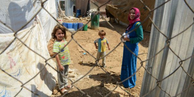 ZAHLE, LEBANON - SEPTEMBER 5, 2013: A Syrian refugee woman seen with her children behind the fence while...
