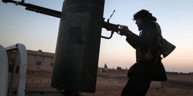 A member of the Islamic Kurdish Front aims at a position of fellow Kurdish fighters from the Committees...