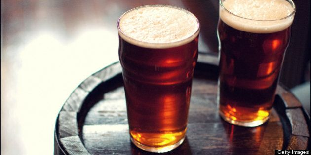 Two pints of beer bitter on wooden barrel in London