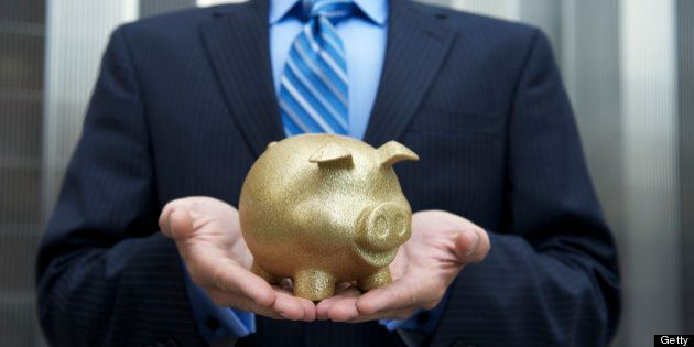 Businessman stands holding a golden piggy bank cradled in his