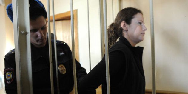 A Russian police officer puts handcuffs on Greenpeace International activist, one of the 'Arctic 30,'...