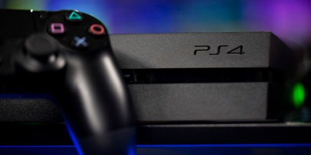 A Sony PlayStation 4 (PS4) controller sits next to the company's games console, manufactured by Sony...