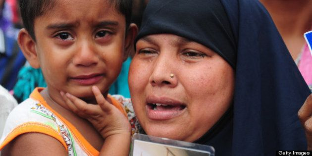 A Bangladeshi woman and her daughter weep as she holds up the portrait of her missing husband, believed...