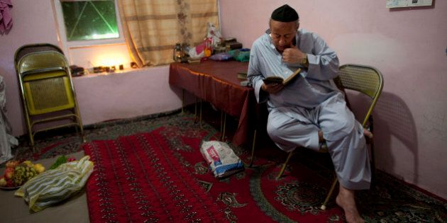 KABUL, AFGHANISTAN - SEPTEMBER 18: Zebulon Simantov reads his old tatered hebrew prayer book as he celebrates...