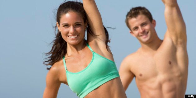 fit couple in sports wear stretching and exercising on the