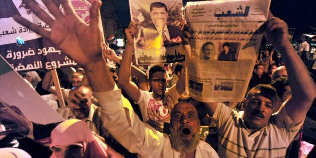 Muslim Brotherhood supporters shout slogans as they wave portraits of Egypt's ousted president Mohamed...
