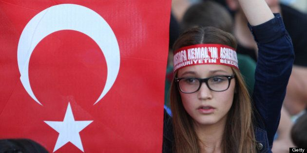 A girl holds a Turkish flag during a demonstration in Ankara on June 4, 2013.  Turkey's Islamic-rooted government said Tuesday it had 'learnt its lesson' and appealed for an end to mass street protests that have convulsed the country for days in the worst political crisis in a decade.  The United Nations joined Washington in pressing for a full investigation into allegations of excessive use of police force against anti-government demonstrators while Turkey's main union federation launched a two-day strike over what it branded 'state terror'. AFP PHOTO / ADEM ALTAN        (Photo credit should read ADEM ALTAN/AFP/Getty Images)