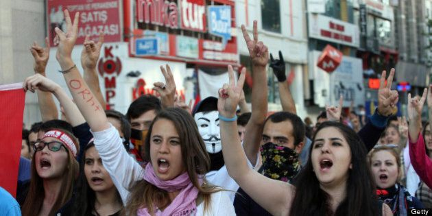 Protesters flash the V for victory sign as they shout anti-government slogans during a demonstration...
