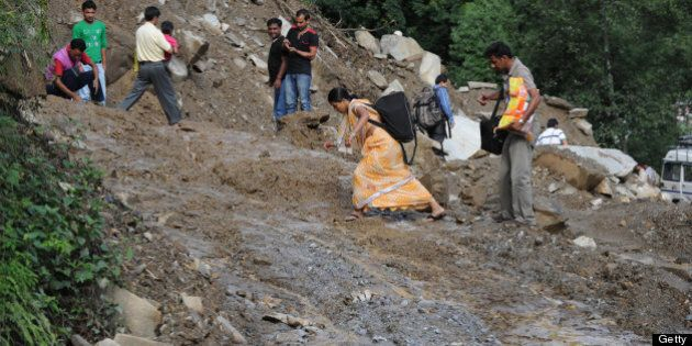 Residents make their way along a damaged roadway to Sonprayag on July 2, 2013, in a flood affected area...