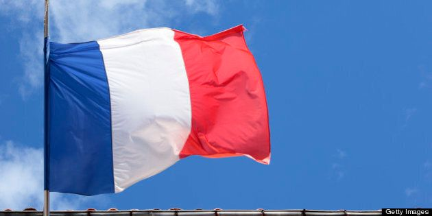 French national flag flying in front of a Government building in