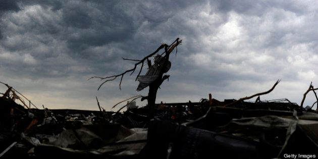 Rain clouds roil over a tornado devastated neighborhood on May 23, 2013 in Moore, Oklahoma. Severe thunderstorms...